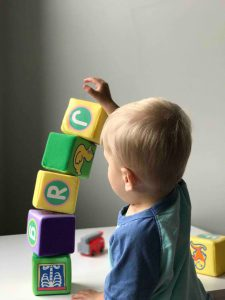 A child builds a tower with toy blocks
