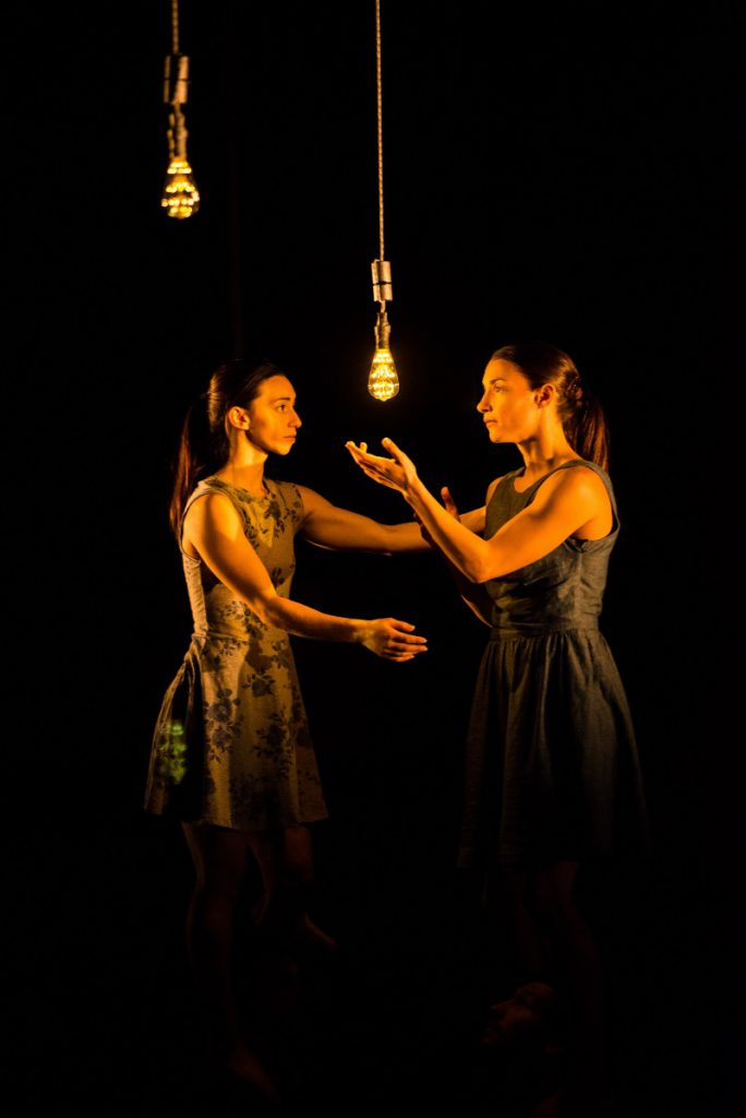 Two women drawn to the energy of a light bulb