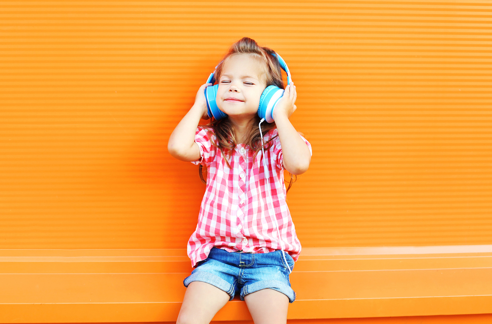 child listening through headphones